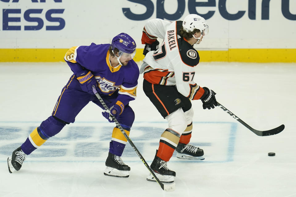 Los Angeles Kings right wing Adrian Kempe (9) defends against Anaheim Ducks center Rickard Rakell (67) during the third period of an NHL hockey game Monday, April 26, 2021, in Los Angeles. (AP Photo/Ashley Landis)