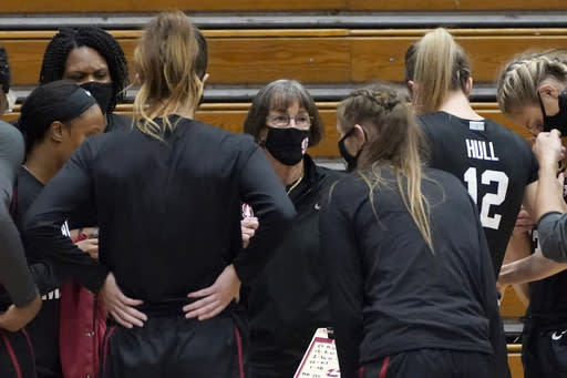 Stanford head coach Tara VanDerveer huddles with her team during a timeout againt Pacific during the firs half of an NCAA college basketball game in Stockton , Calif., Tuesday, Dec. 15, 2020. With a win over Pacific, VanDerveer will become the winningest women's coach in history breaking Pat Summitt's record of 1,098. (AP Photo/Rich Pedroncelli)