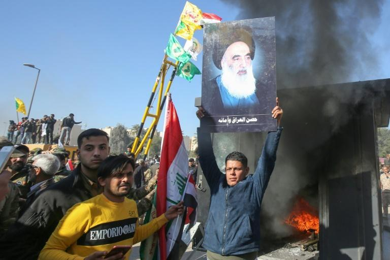 An Iraqi supporter of the Hashed al-Shaabi paramilitary network lifts a picture of Iraq's top Shiite cleric Grand Ayatollah Ali Sistani in front of the US embassy in Baghdad