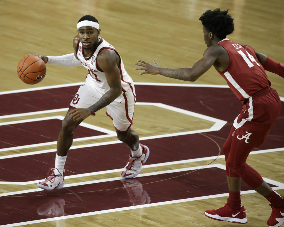 Oklahoma's De'Vion Harmon (11) dribbles against Alabama's Keon Ellis (14) during the second half of an NCAA college basketball game in Norman, Okla., Saturday, Jan. 30, 2021. (AP Photo/Garett Fisbeck)