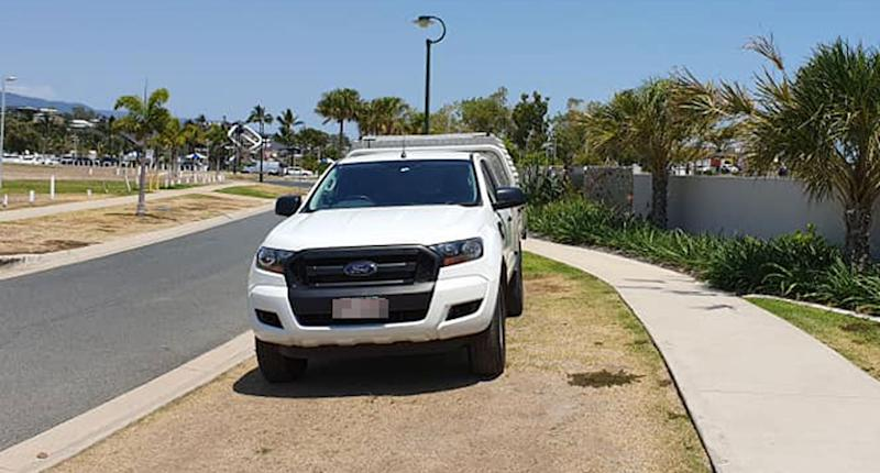 A ute is seen parked on a nature strip next to a footpath in Cannonvale in the Whitsundays.