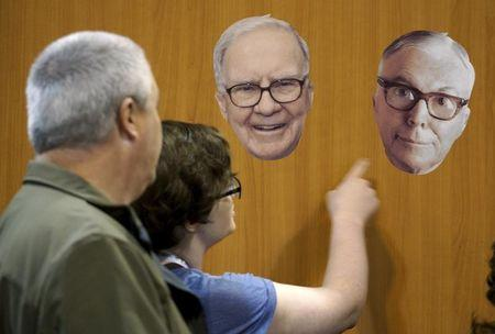 Berkshire Hathaway shareholders look at photos of Berkshire CEO Warren Buffett (L) and vice-chairman Charlie Munger at the Berkshire-owned Fruit of the Loom booth at the shareholder's shopping day in Omaha, Nebraska May 1, 2015.  The annual meeting takes place May 2, 2015.  REUTERS/Rick Wilking