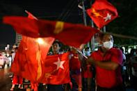 Supporters of the National League for Democracy (NLD) party wave the party's flag in front of itsheadquarters in Yangon on November 8, 2020, as votes are counted after polls closed in Myanmar's election