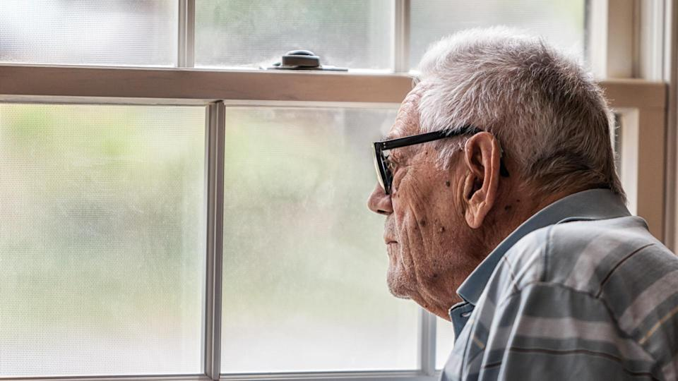 A hearing impaired elderly senior adult man wearing a hearing aid is sitting staring through the hazy, speckled, unwashed window and grungy mesh screen of a living room window at home.
