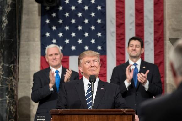 President Donald Trump with Vice President Mike Pence and House Speaker Paul Ryan standing behind him