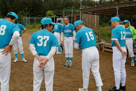Koji Otomo, a retired teacher and head of the Shimohama Club baseball team, talks with his team members during their training session in Akita