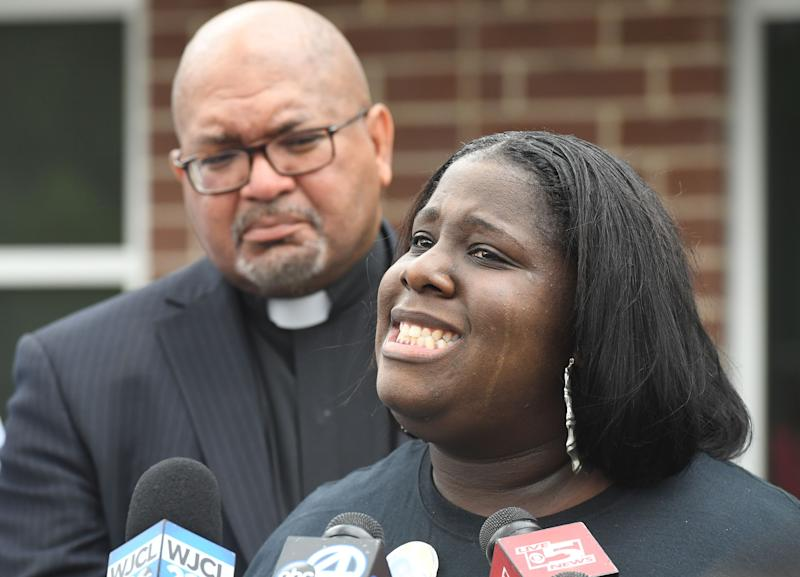 Rev. Perry Griffin stands behind Ashley Wright as she talks to media about her daughter, Raniya Wright, outside the Colleton County Sheriff Administration building Friday, April 19, 2019.