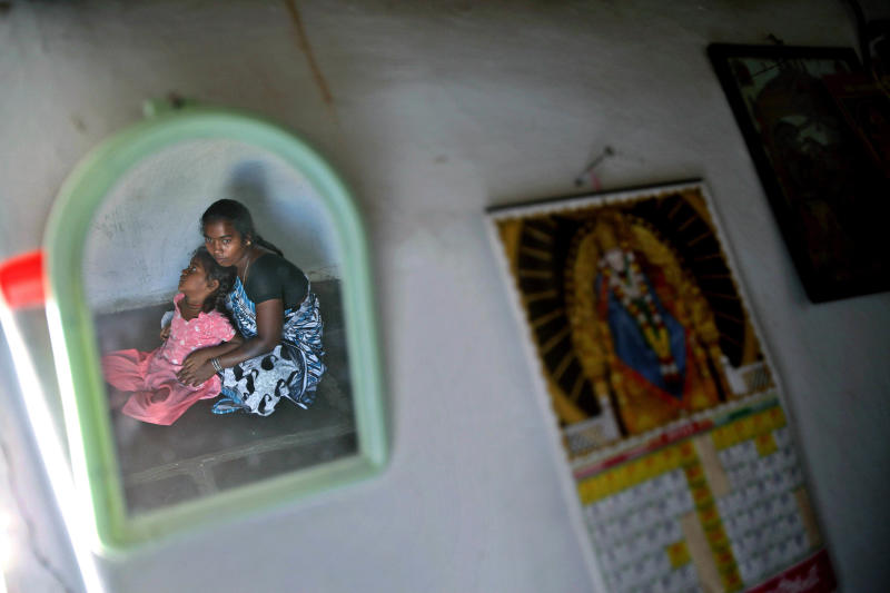 In this photo taken Feb. 14, 2012, Sunita, 22, right, and her daughter Shwetha, 5, are reflected in a mirror hanging on the wall of their house where Sunita's debt-ridden husband Hari Prasad consumed fertilizer chemical to kill himself on Aug. 1, 2010, in Kadiri village about 160 kilometers (99 miles) north of Bangalore, India. A wave of suicides among the impoverished residents of India's Andhra Pradesh state was blamed on the relentless tactics of agents from microfinance companies, which give small loans intended to lift up the very poor. (AP Photo/Aijaz Rahi)