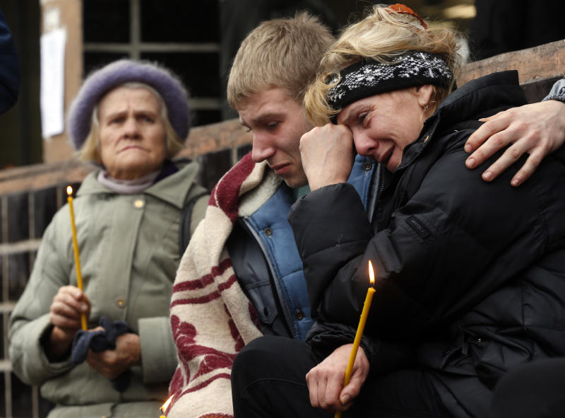 Passers by react outside the collapsed Maxima supermarket in Riga, Latvia, Saturday, Nov. 23, 2013. Scores of people have died, including three firefighters, after an enormous section of roof collapsed at a Latvian supermarket in the country's capital, emergency medical officials said Friday. The reason for the collapse during shopping rush-hour Thursday was still not known but rescue and police officials said that possible theories include building's design flaws and poor construction work. (AP Photo/Mindaugas Kulbis)