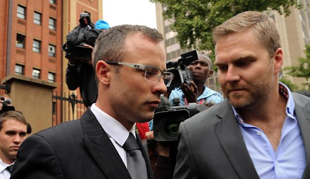 Oscar Pistorius, left, with unidentified relative leaves the high court in Pretoria, South Africa, Thursday, April 17, 2014. Pistorius is charged with murder for the shooting death of his girlfriend, Reeva Steenkamp, on Valentines Day in 2013. (AP Photo/Themba Hadebe)