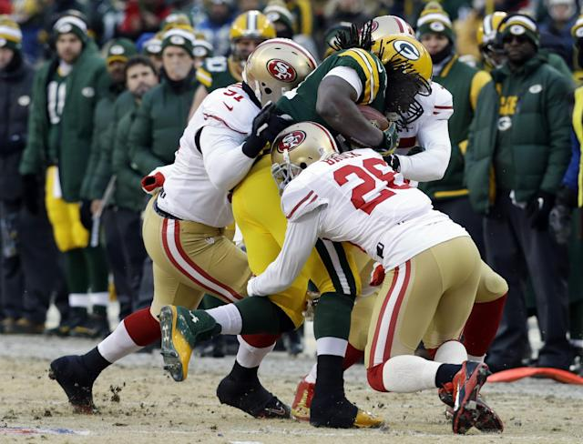 Green Bay Packers running back Eddie Lacy (27) gets tackled by San Francisco 49ers defensive end Ray McDonald (91) and cornerback Tramaine Brock (26) during the first half of an NFL wild-card playoff football game, Sunday, Jan. 5, 2014, in Green Bay, Wis. (AP Photo/Mike Roemer)