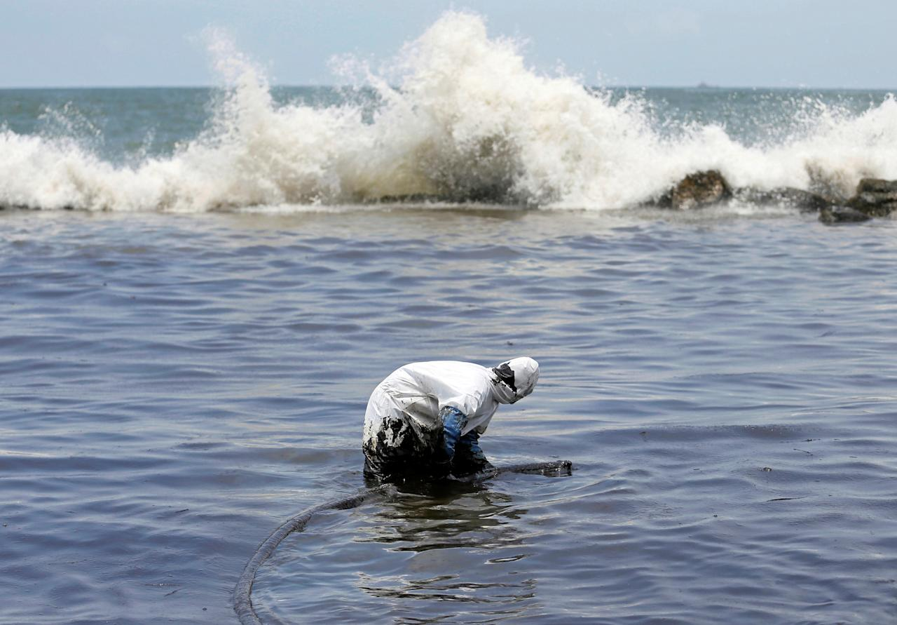 <p>A member of the Sri Lankan coast guard removes oil from a beach after an oil spill in Uswetakeiyawa, Sri Lanka September 10, 2018. REUTERS/Dinuka Liyanawatte </p>