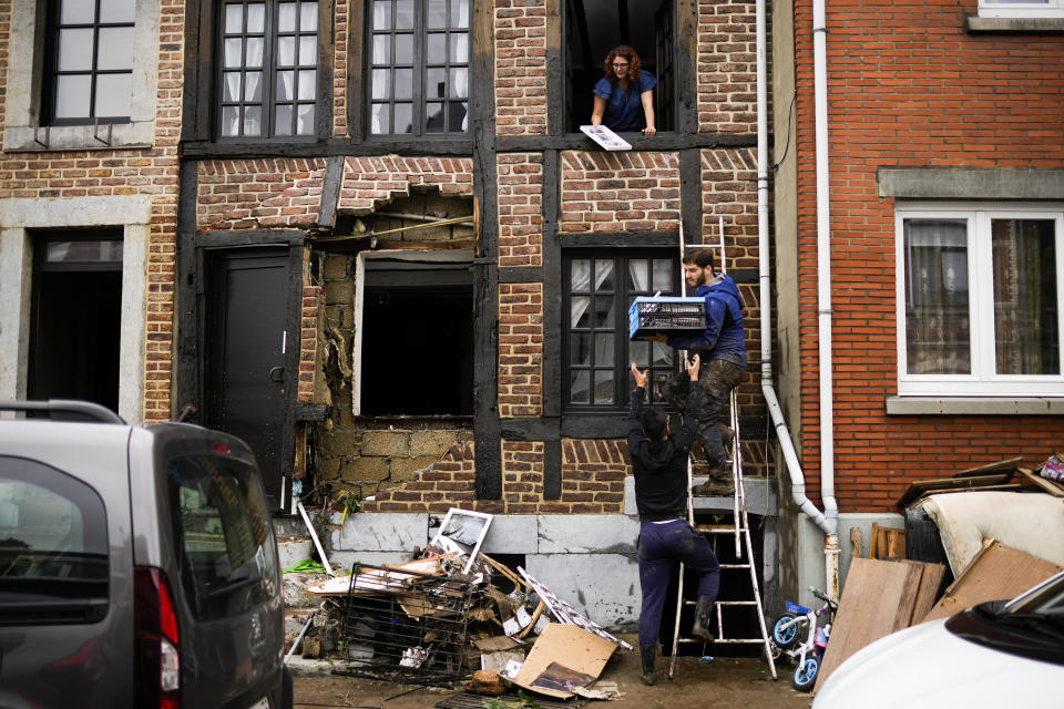 A man carries belongings down a ladder in a crate after flooding in Ensival, Verviers, Belgium, Friday July 16, 2021. Severe flooding in Germany and Belgium has turned streams and streets into raging torrents that have swept away cars and caused houses to collapse. (AP Photo/Francisco Seco)