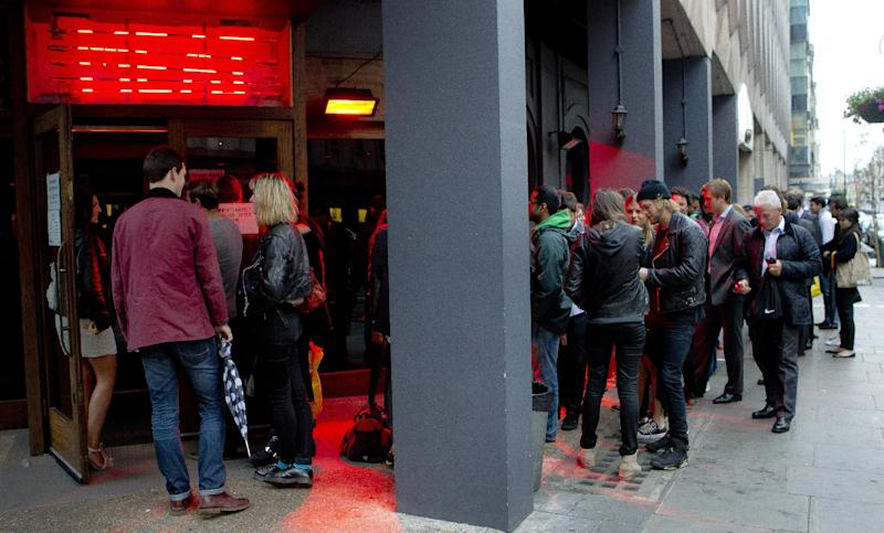 FOR STORY DINING DELAYS - Customers form a queue as they wait to be seated in the Meat Liquor restaurant on Welbeck Street in central London, around 20:30 on Tuesday, July 10, 2012, which is currently one of London's busiest destinations for burgers and cocktails.  The Meat Liquor restaurant has a no-booking policy which means queues often form outside as customers wait to sample the food and the atmosphere at one of the capital's most sought after destinations, but people have to arrive together if they want to be seated together.  (AP Photo/Joel Ryan)