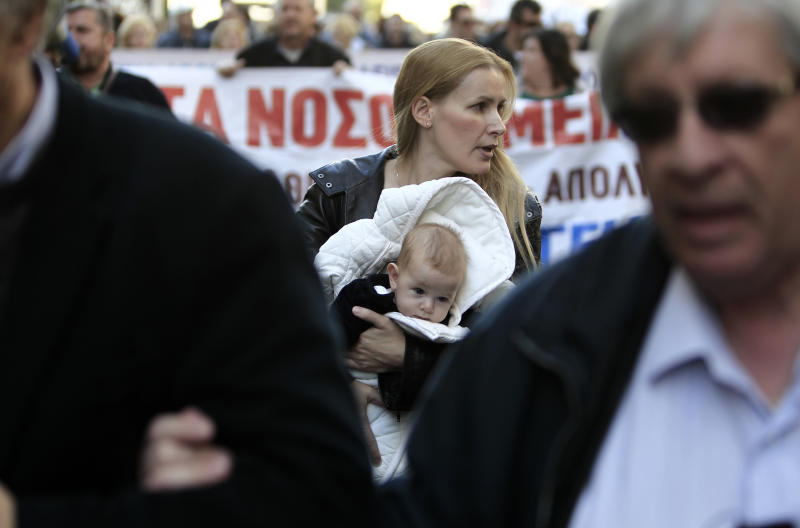 A doctor with her son, name not given, takes part in a protest in Athens, Friday, Nov. 29, 2013. Greek state hospitals are functioning with emergency staff as doctors and staff hold a 24-hour strike against planned health cutbacks enforced under the country's harsh austerity program. Unions are angry at the conservative-led government's plans to suspend and reallocate staff as part of its drive to reform the public sector and reduce the budget deficit. (AP Photo/Thanassis Stavrakis)