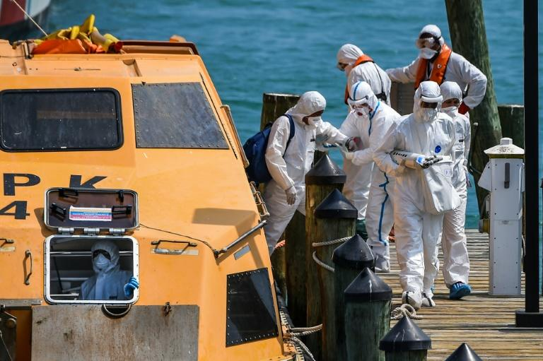 Medics assist sick crew members as they arrive in Miami on March 26 (AFP Photo/CHANDAN KHANNA)