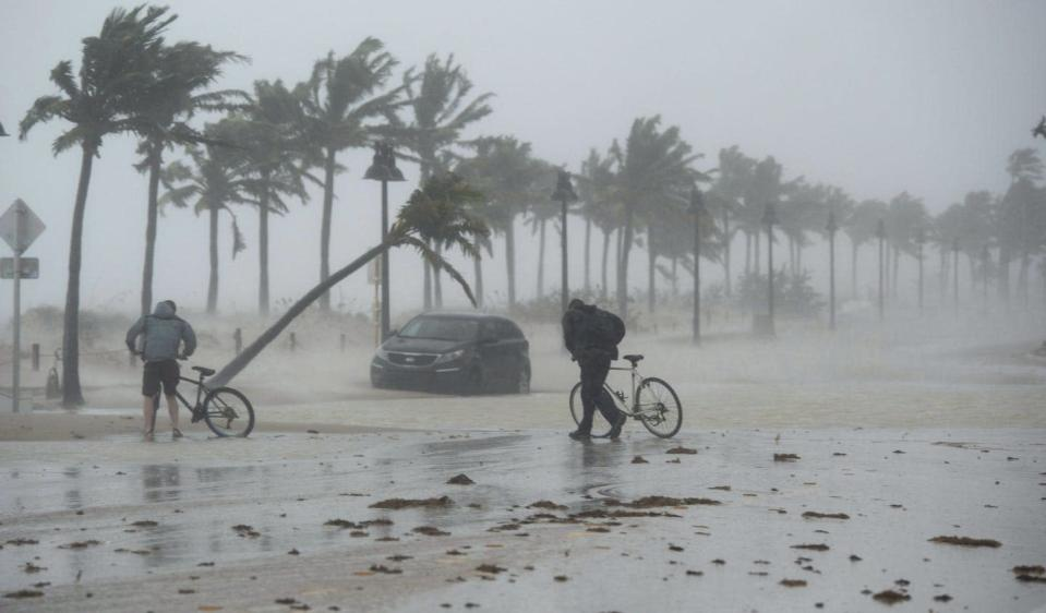 "<span class=""caption"">Two people walk their bicycles along a flooded street on the waterfront of Fort Lauderdale, Fla., as Hurricane Irma passes through on Sept. 10, 2017. </span> <span class=""attribution""><span class=""source"">THE CANADIAN PRESS/Paul Chiasson</span></span>"