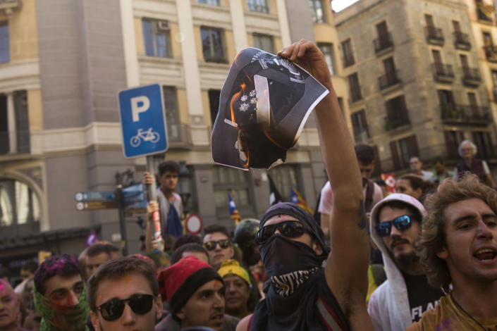 A pro independence demonstrator burns a poster with the portrait of the Spanish King Felipe IV, during clashes with Catalan police officers on their way to meet demonstrations by member and supporters of National Police and Guardia Civil, in Barcelona on Saturday, Sept. 29, 2018. (AP Photo/Emilio Morenatti)