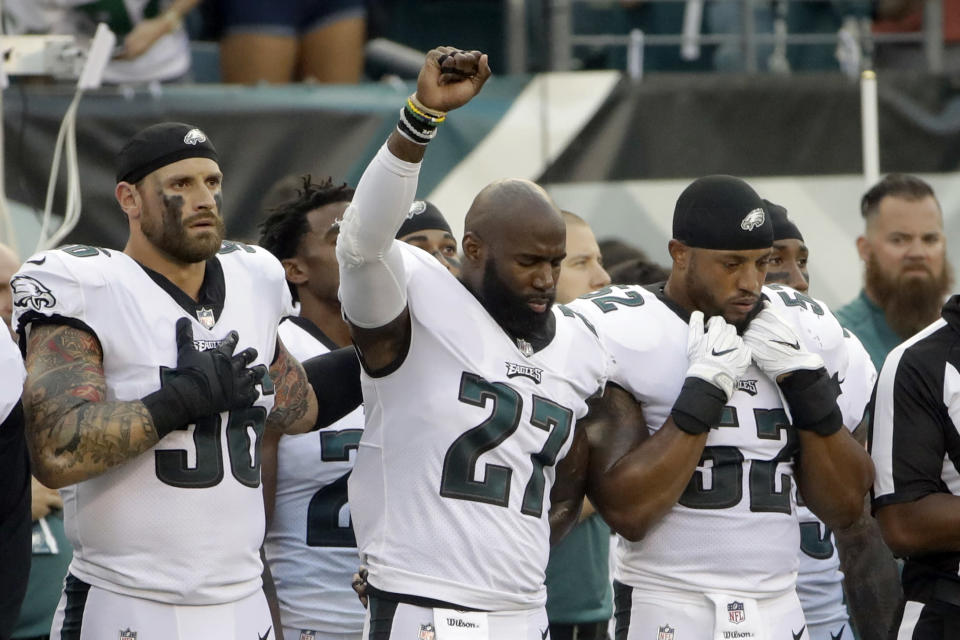 Chris Long (56) supports Malcolm Jenkins (27) during his protest Thursday night. (AP)