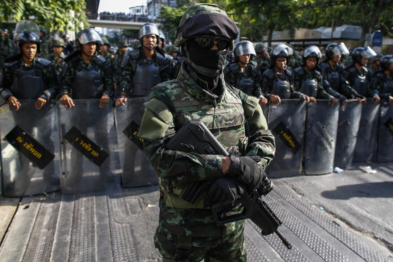 "Thai soldiers stand guard as they block a street during a protest against military rule in central Bangkok May 24, 2014. Former Prime Minister Yingluck Shinawatra was in a ""safe place"" on Saturday, an aide said, after being held by Thailand's army following its seizure of power this week, as opposition to the coup grew among her supporters and pro-democracy activists. REUTERS/Athit Perawongmetha (THAILAND - Tags: POLITICS CIVIL UNREST MILITARY TPX IMAGES OF THE DAY)"