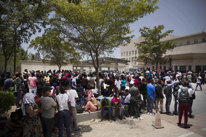 People gather in front of the U.S. Embassy in Port-au-Prince, Haiti, Friday, July 9, 2021. A large crowd gathered outside the embassy amid rumors on radio and social media that the U.S. will be handing out exile and humanitarian visas, two days after Haitian President Jovenel Moïse was assassinated in his home. (AP Photo/Joseph Odelyn)