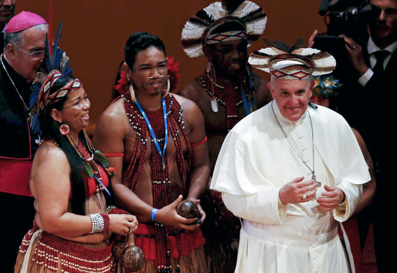 Pope Francis wears an indigenous feathered hat given to him by representatives of one of Brazil's native tribes during a meeting at the Municipal Theater in Rio de Janeiro, Brazil, Saturday, July 27, 2013. Pope Francis is on the sixth day of his trip to Brazil where he will attend the 2013 World Youth Day in Rio. (AP Photo/Monica Imbuzeiro, Agencia O Globo)