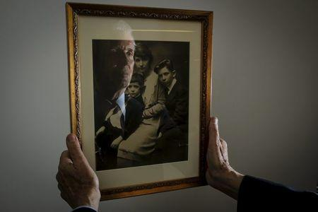 Alexander Sanger, Chair of the International Planned Parenthood Council, is reflected in a photograph of his Grandmother Margaret Sanger and her two sons Stuart Sanger and Grant Sanger (R) as he poses for a photo in the Manhattan borough of New York, December 12, 2015. Grant Sanger is Alexander's father and Margaret Sanger was the founder of Planned Parenthood. REUTERS/Carlo Allegri