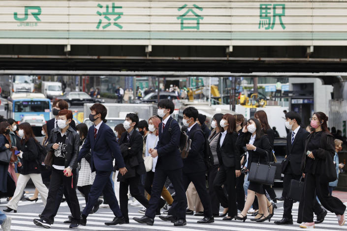 People wearing face masks cross an intersection in the downtown in Tokyo, Japan, Thursday, April 8, 2021. Tokyo, the capital of Japan, has asked the central government for permission to implement emergency measures to curb a surge in a rapidly spreading and more contagious coronavirus variant, just over three months before the start of the Olympics. (Kyodo News via AP)