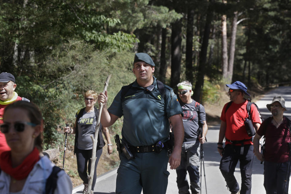 A civil guard leads volunteers searching in woodland area in Cercedilla, just outside of Madrid, Spain, Tuesday, Sept. 3, 2019. A search squad of hundreds is combing a mountainous area outside Madrid 11 days after former alpine ski racer and Olympic medalist Blanca Fernandez Ochoa went missing.(AP Photo/Paul White)