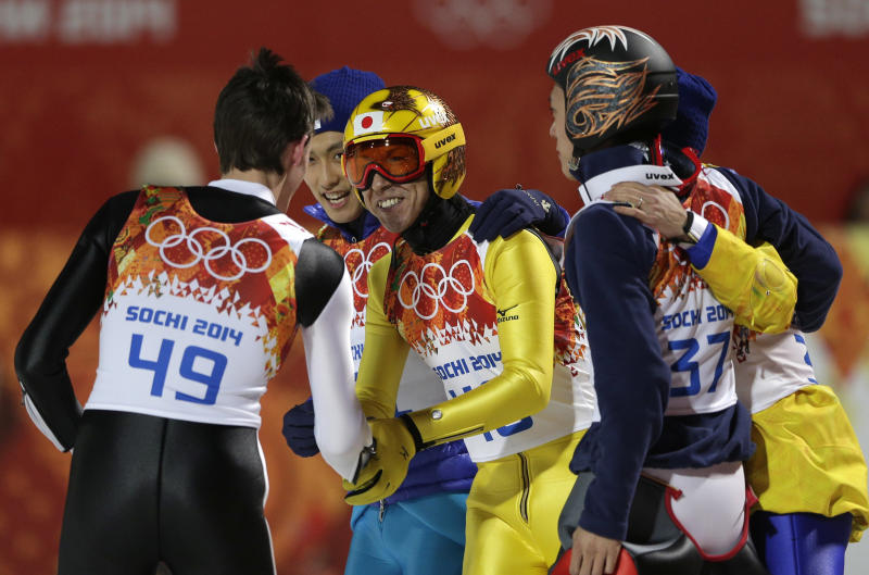 Japan's silver medal winner Noriaki Kasai congratulates Slovenia's bronze medal winner Peter Prevc, left, during the ski jumping large hill final at the 2014 Winter Olympics, Saturday, Feb. 15, 2014, in Krasnaya Polyana, Russia. (AP Photo/Matthias Schrader)