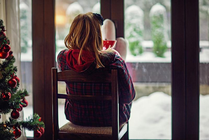 Young woman is looking the falling snow outside