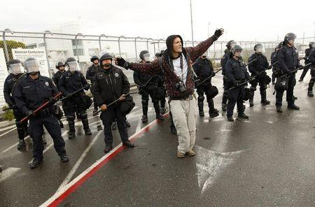 A protester gestures in front of a line of police officers in riot gear during the Occupy movement's attempts to shut down West Coast ports in Oakland, California December 12, 2011. REUTERS/Robert Galbraith