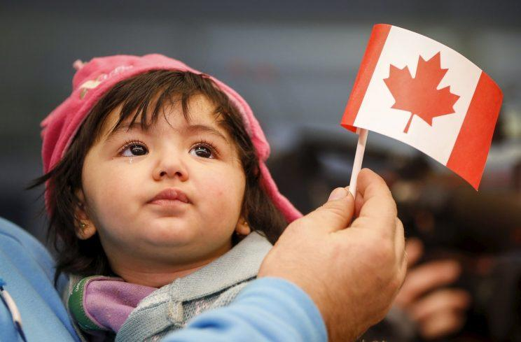 A Syrian refugee looks up as her father holds her and a Canadian flag as they arrive at Pearson Toronto International Airport in Mississauga, Ontario, December 18, 2015. Photo from REUTERS.