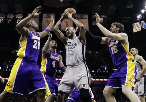 San Antonio Spurs' Tim Duncan (21) grabs a rebound between Los Angeles Lakers' Jodie Meeks (20), Antawn Jamison (4) and Pau Gasol (16) during the first half of Game 1 of their first-round NBA playoff basketball series, Sunday, April 21, 2013, in San Antonio. (AP Photo/Eric Gay)