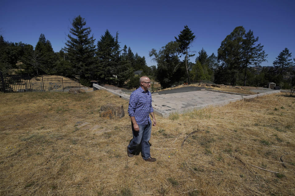 """Will Abrams walks on the lot of his family home that was destroyed by wildfires in 2017 while interviewed in Santa Rosa, Calif., Thursday, June 24, 2021. """"I have been really disappointed,"""" Abrams said. """"The bankruptcy was sold as something that was going to hold PG&E to account, and it was not. Bankruptcy is not a process to reorganize. It is a process to divide up the dollars."""" (AP Photo/Jeff Chiu)"""