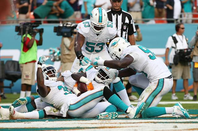 Miami Dolphins Michael Thomas, center, is congratulated by teammates Chris Clemons (30), left, and Jelani Jenkins (53) after Thomas intercepted a pass intended for New England Patriots wide receiver Austin Collie (10) during the second half of an NFL football game, Sunday, Dec. 15, 2013, in Miami Gardens, Fla. The Dolphins defeated the Patriots 24-20. (AP Photo/J Pat Carter)