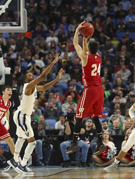 Wisconsin guard Bronson Koenig (24) takes a three-point shot against Villanova guard Mikal Bridges (25) during the second half of a second-round men's college basketball game in the NCAA Tournament, Saturday, March 18, 2017, in Buffalo, N.Y. Wisconsin won, 65-62. (AP Photo/Bill Wippert)