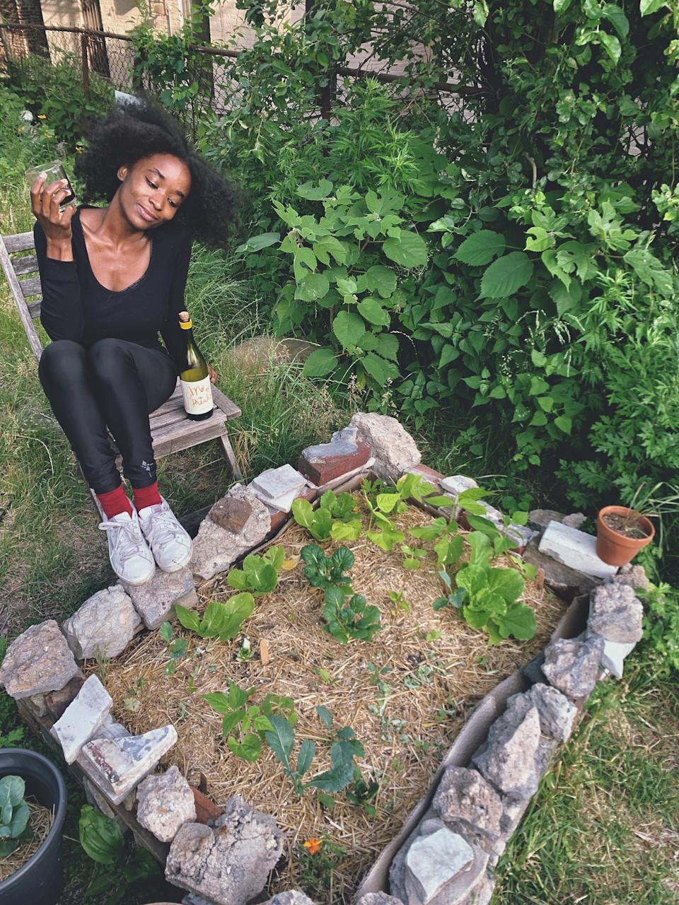 """Brionna Jimerson sits by one of her raised garden beds in Brooklyn, N.Y. """"There is something inherently powerful about being able to produce and cultivate something with your own two hands,"""" Jimerson says."""