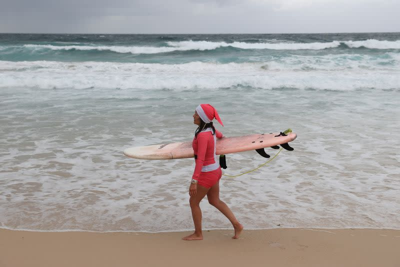 A surfer wears a Christmas-themed outfit on Christmas Day at Bondi Beach in Sydney