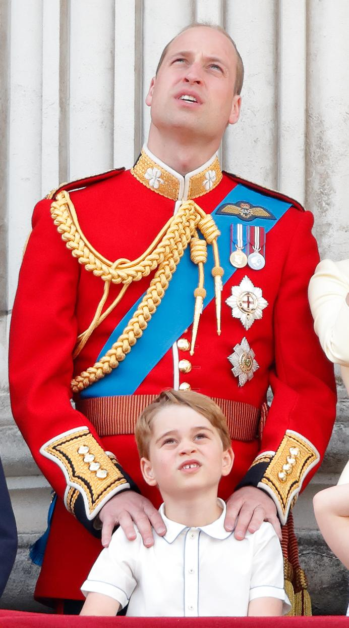 LONDON, UNITED KINGDOM - JUNE 08: (EMBARGOED FOR PUBLICATION IN UK NEWSPAPERS UNTIL 24 HOURS AFTER CREATE DATE AND TIME) Prince William, Duke of Cambridge places his hands on Prince George of Cambridge's shoulders as they watch a flypast from the balcony of Buckingham Palace during Trooping The Colour, the Queen's annual birthday parade, on June 8, 2019 in London, England. The annual ceremony involving over 1400 guardsmen and cavalry, is believed to have first been performed during the reign of King Charles II. The parade marks the official birthday of the Sovereign, although the Queen's actual birthday is on April 21st. (Photo by Max Mumby/Indigo/Getty Images)