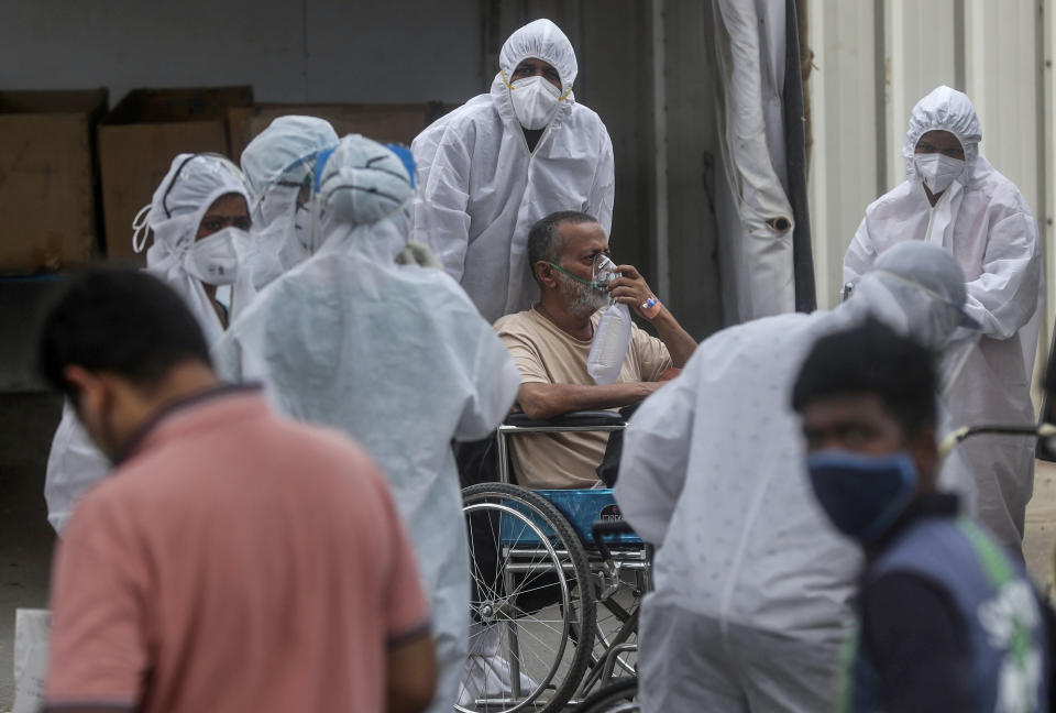 Health workers attend to a patient at the Jumbo COVID-19 filed hospital in Mumbai, India, Monday, April 26, 2021. New infections are rising faster in India than any other place in the world, stunning authorities and capsizing its fragile health system. (AP Photo/Rafiq Maqbool)