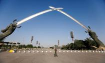 """FILE PHOTO: An Iraqi security officer walks near the """"Arch of Victory"""" memorial in the Green Zone of Baghdad"""