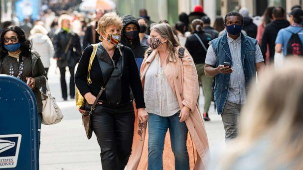 PHOTO: People wear face masks while walking on Fifth Avenue, April 10, 2021, in New York. (Noam Galai/Getty Images)