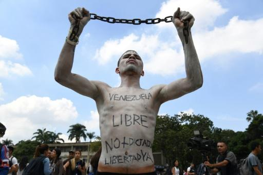 A university student holds a chain with his body painted during a protest against Venezuela's President Nicolas Maduro in Caracas in November 2019