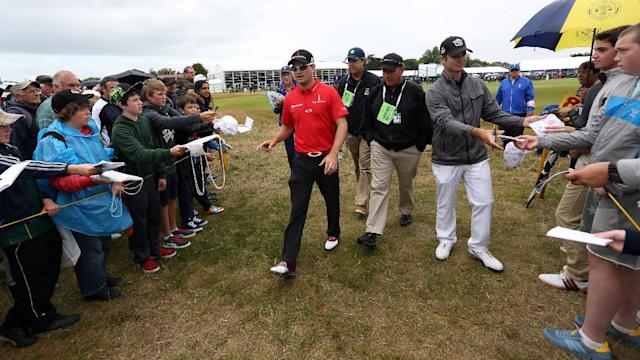 Zach Johnson of the US, left, and Kevin Streelman of the US, right, walk past spectators asking for autographs after playing the 3rd hole during a practice round ahead of the British Open Golf championship at the Royal Liverpool golf club, Hoylake, England, Wednesday July 16, 2014. The British Open Golf championship starts Thursday July 17. (AP Photo/Jon Super)