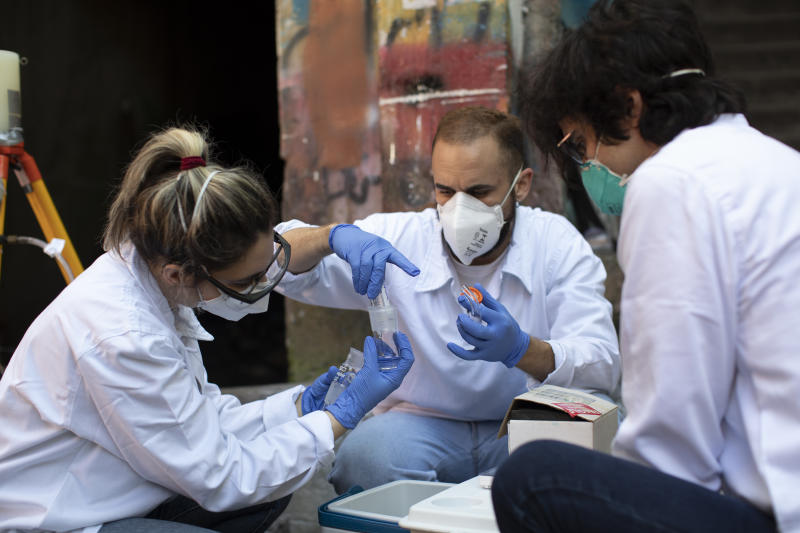 Researchers of the Rio de Janeiro State University prepare an instrument to sample airborne sewage droplets for the presence of the new coronavirus at the Santa Marta slum, in Rio de Janeiro, Brazil, Monday, July 27, 2020. The researchers are working together with volunteers of a local sanitation team to see if they can detect the virus in the air and evaporation from the slum's open-air sewers. (AP Photo/Silvia Izquierdo)