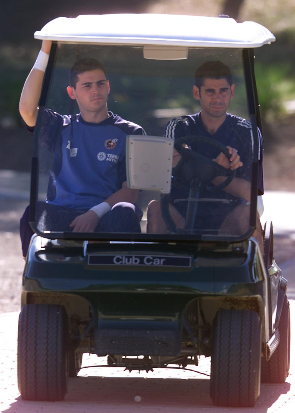 Iker Casillas(L) and Fernando Hierro of the Spanish national soccer  team travel by golf cart to a warm-up session at Montecastillo training  ground near Jerez, May 19, 2002. Spain are preparing for the World Cup  finals in Korea and Japan. REUTERS/Marcelo del Pozo    MDP/CLH/