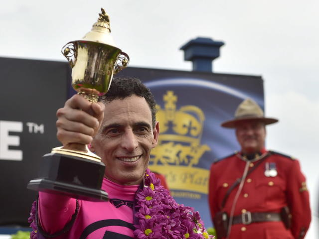 Jockey John Velazquez holds the trophy after winning the Queen's Plate horse race aboard Wonder Gadot at Woodbine Racetrack in Toronto on Saturday, June 30, 2018. (Frank Gunn/The Canadian Press via AP)