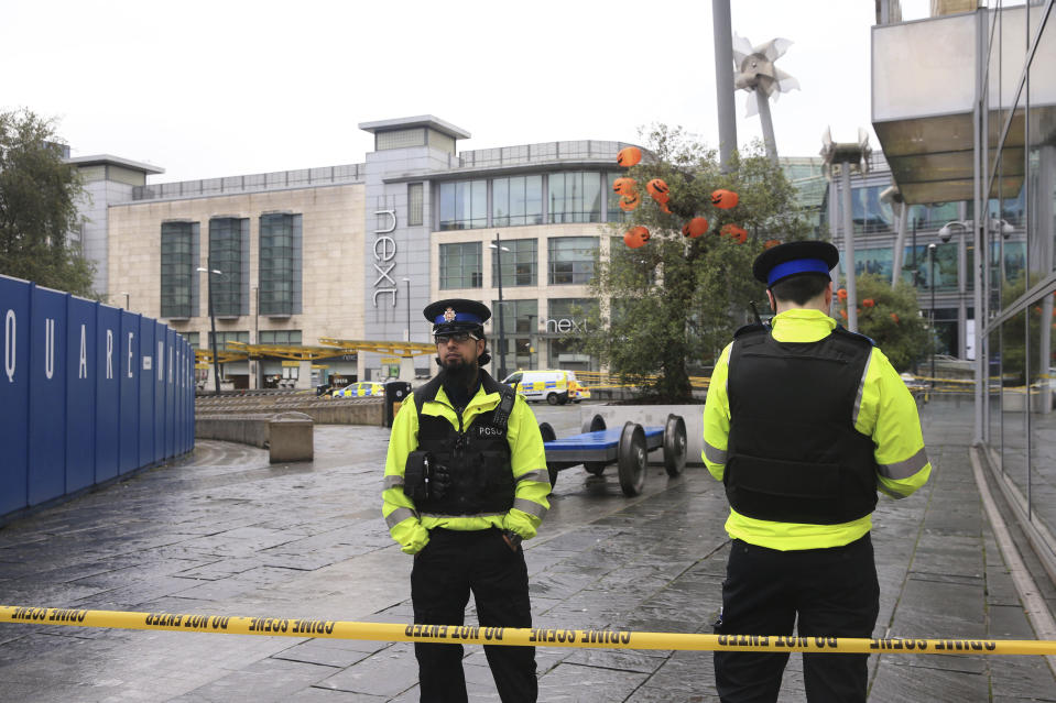 Police outside the Arndale Centre in Manchester, England, Friday October 11, 2019, after a stabbing incident at the shopping center that left four people injured. Greater Manchester Police say a man in his 40s has been arrested on suspicion of serious assault. He had been taken into custody. (Peter Byrne/PA via AP)
