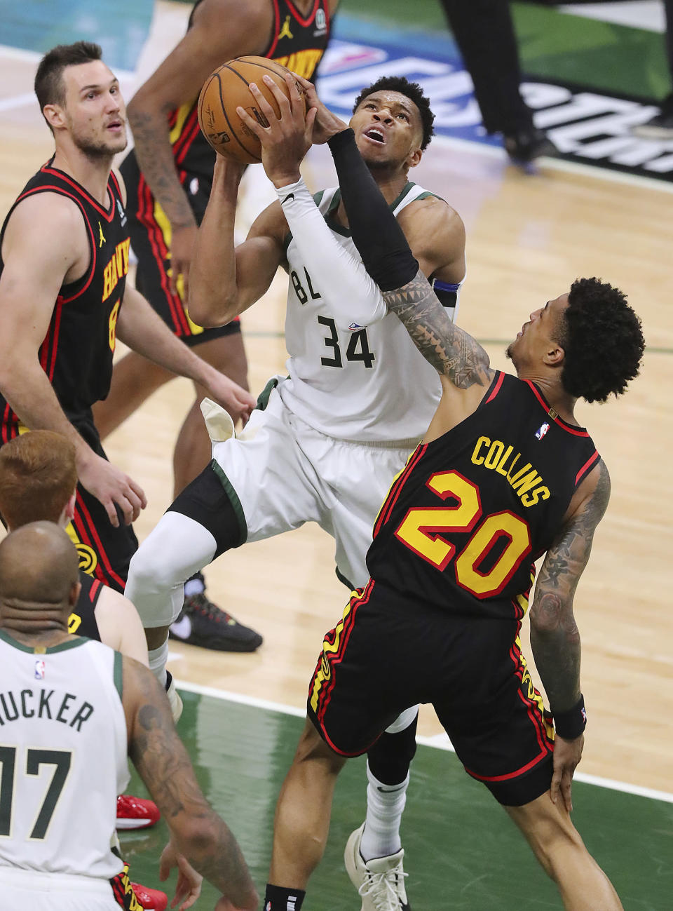 Atlanta Hawks forward John Collins fouls Milwaukee Bucks forward Giannis Antetokounmpo on his way to the basket during the first half of game 2 in the NBA Eastern Conference Finals on Friday, June 25, 2021, in Milwaukee. (Curtis Compton/Atlanta Journal-Constitution via AP)